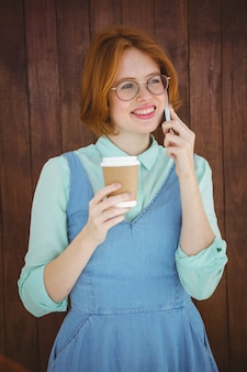 Hipster praten over telefoon met koffie