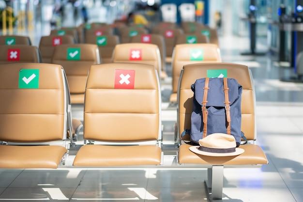 Hipster rugzak en hoed op stoel in internationale luchthaven. new normal, reisbel en sociale afstandsconcepten, bescherming coronavirus (covid-19) infectie