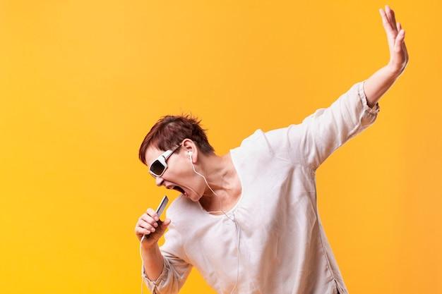 Hipster senior vrouw zingen en luisteren muziek