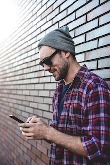 Hipster sms-telefoonapp in stad straat op bakstenen muur achtergrond. geweldige man met smartphone in slimme vrijetijdskleding staan. stedelijke jonge professionele levensstijl.