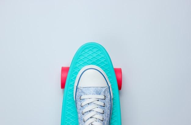 Hipster sneakers op skateboard bovenaanzicht op achtergrond. minimalisme levensstijl concept. kopie ruimte