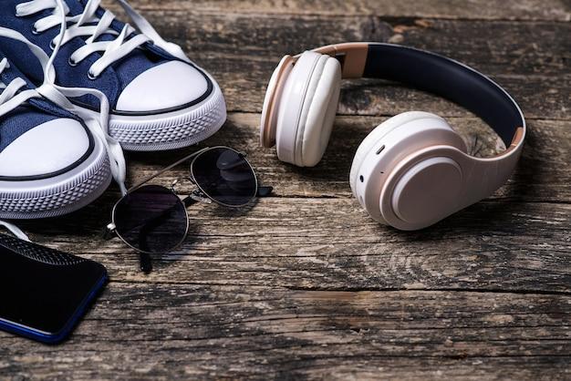 Hipster stedelijke stijl. koptelefoons en sneakers op houten rustieke tafel. set trendy herenaccessoires.