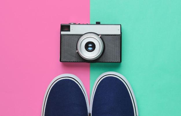 Hipster-stijl plat gelegd. klassieke sneakers en retro filmcamera op een pastelkleurige achtergrond. bovenaanzicht
