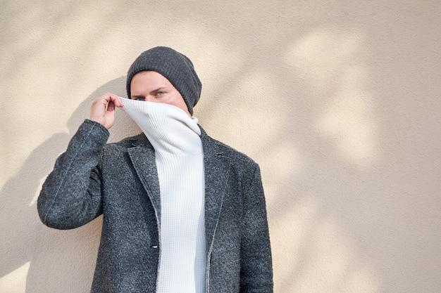 Hipster stijlvolle man met een modieuze grijze jas gezicht met witte trui verbergen.