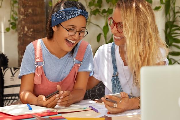 Hipster-studenten zoeken informatie op internetwebsite, lachen gelukkig als grappige foto in mobiele telefoon opmerken, poseren samen op desktop met laptop en kladblok, genieten van communicatie