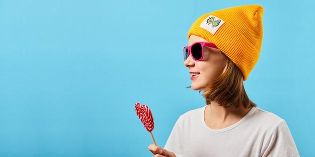 Hipster tiener meisje in trendy bril gebreide muts dragen en lolly te houden. vrij modieuze vrouw met een snoepje in de buurt van het gezicht.