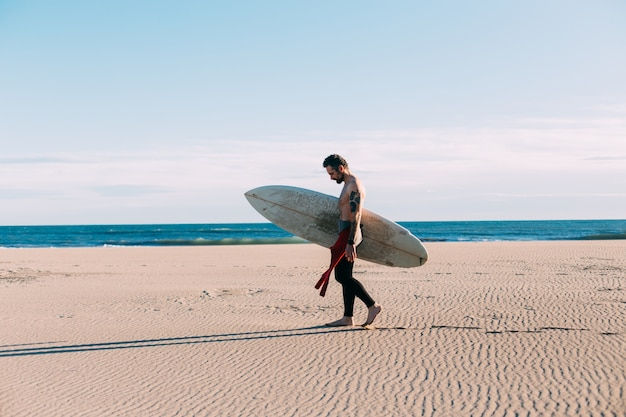 Hipster trendy surfer op strand met surfboard