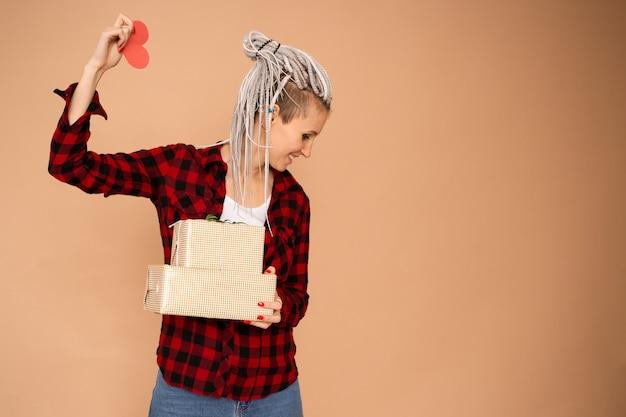 Hipster trendy vrouw met dreadlocks op saint valentine's day met rood hart valentijn en geschenkdozen geïsoleerd op beige achtergrond
