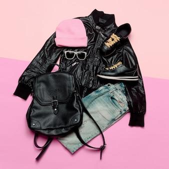 Hipster urban outfit meisje stijlvolle zwarte kleding en felle accessoires stijlvolle rugzak en muts