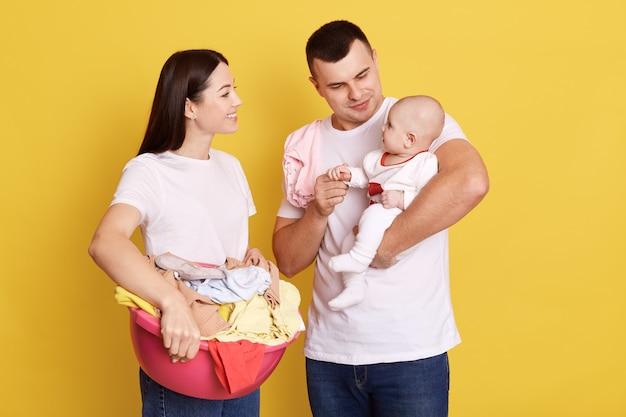 Hipster vader en moeder poseren met hun kind geïsoleerd over gele muur, aantrekkelijke vrouw met bekken met kleding, was doen, schattige babymeisje op papa's handen.