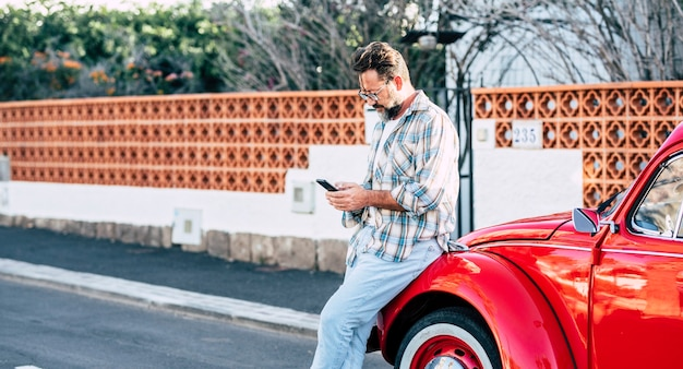 Hipster volwassen man die buiten de auto staat en tekst op moderne telefoon - planning van bestemmingsreizen mensen met mobiele verbinding - voertuigeigenaar stuurt bericht op smartphone