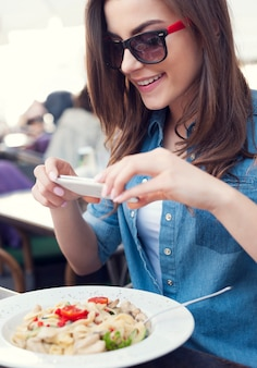 Hipster vrouw die een foto van italiaanse maaltijd neemt