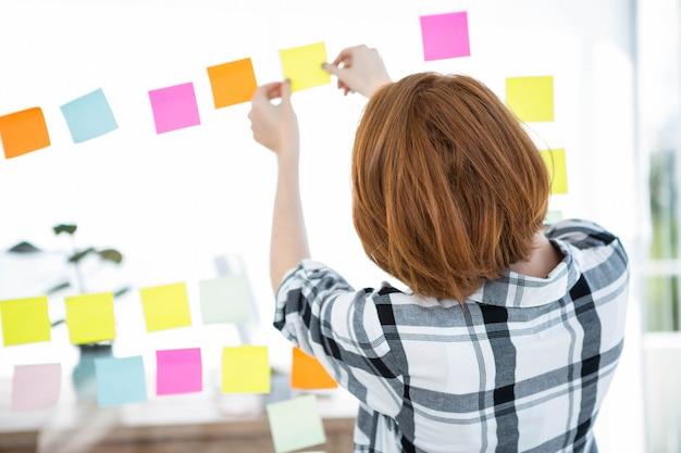 Hipster vrouw geconfronteerd weg van de camera, steekt gekleurd papier omhoog suares