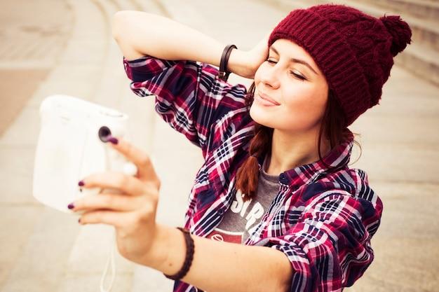 Hipster vrouw in casual outfit zittend op trappen in de stad, selfie maken op instant camera
