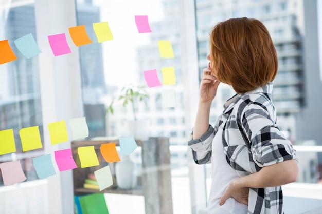 Hipster vrouw stond in haar kantoor, starend naar een muur van notities