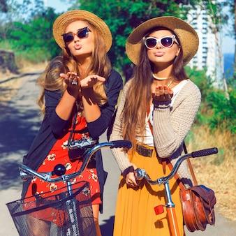 Hipster vrouwenvrienden die een kus blazen. lekker samen wandelen met fietsen in het park aan zeezijde.