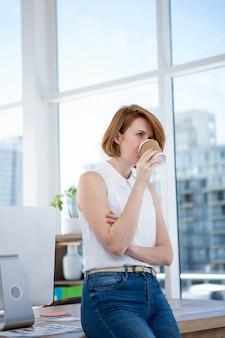 Hipster zakenvrouw zittend op een bureau, koffie drinken