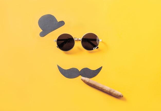 Hipster zonnebril en grappige snor met hoed en sigaar op geel