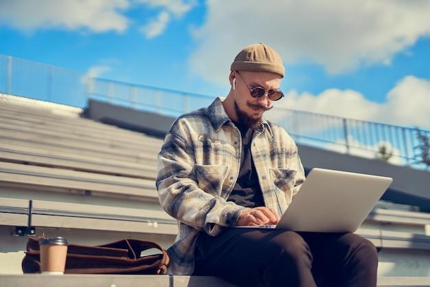 Hipsterblogger in stijlvolle brillen die inhoudstekst typt om nieuwe volgers naar een eigen website te trekken