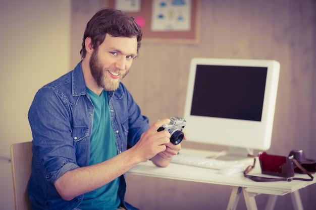 Hipsterfotograaf die zijn camera bekijkt