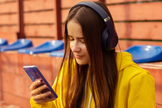 Hipstermeisje geniet van favoriete muzieknummer in draadloze koptelefoon op een zonnige dag in het stadion