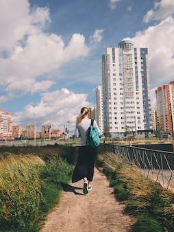 Hipstermeisje met een rugzak is op de weg