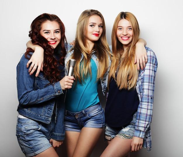 Hipstermeisjes met een microfoon die zingen en plezier hebben