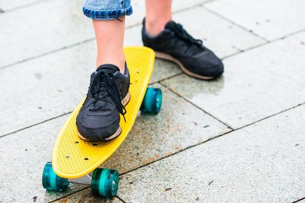 Hipstermeisjes met skateboard in openlucht in de regen. close-up skatebord. actieve sportieve vrouw die pret in skatepark heeft.