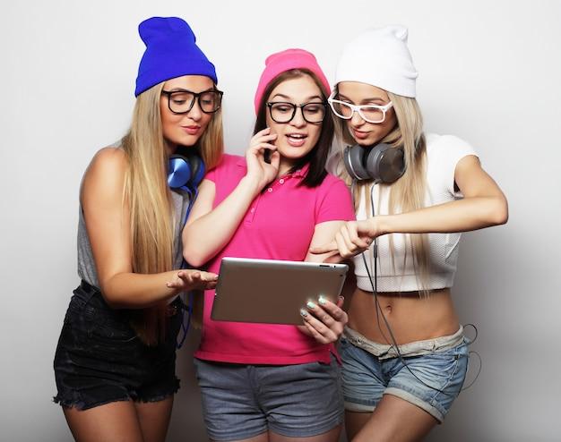 Hipstermeisjesvrienden met digitale tablet over witte muur
