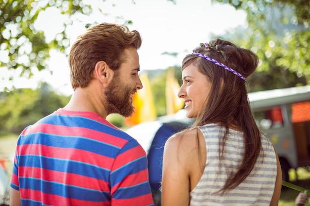 Hipsterpaar die bij elkaar bij een muziekfestival glimlachen