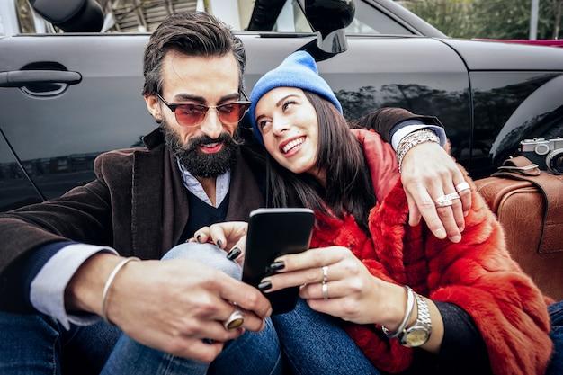 Hipsterpaar die pret met mobiele slimme telefoon hebben bij auto roadtrip