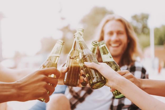 Hipsters drinken bier op het strand in zonlicht.
