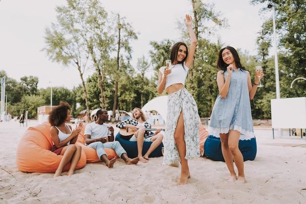 Hipsters spelen gitaarzang en dansen op strand