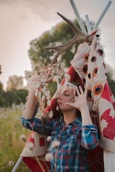 Hipstervrouw in de vorm van een sjamaan zoekt inspiratie van moeder aarde in een wigwam in de natuur.