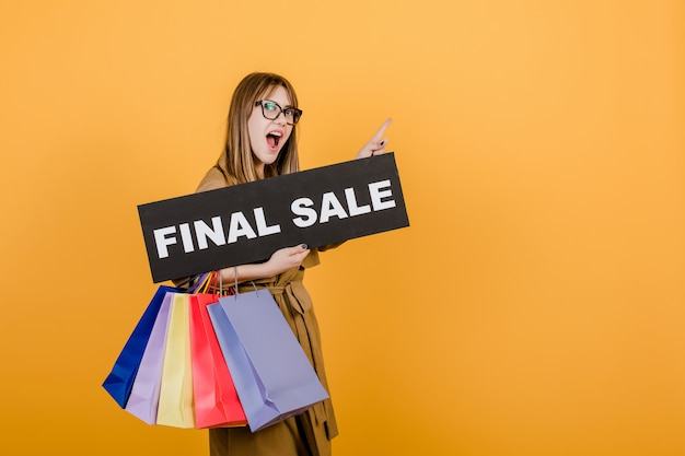 Hipstervrouw in glazen en laag met definitief verkoopteken en kleurrijke die het winkelen zakken over geel wordt geïsoleerd