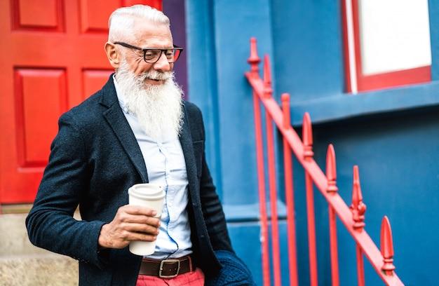 Hipsterzakenman die met meeneemkop van koffiemuur lopen