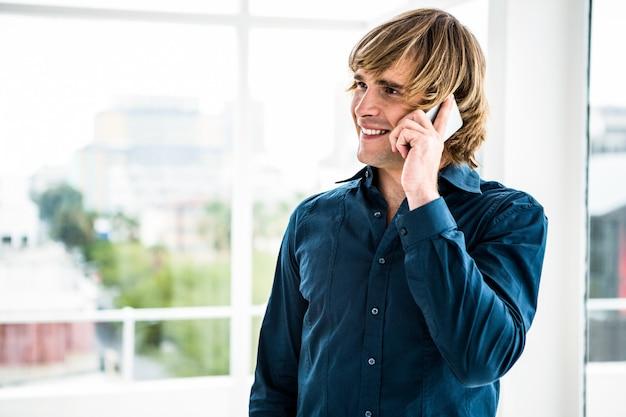Hipsterzakenman die op de telefoon in bureau spreken