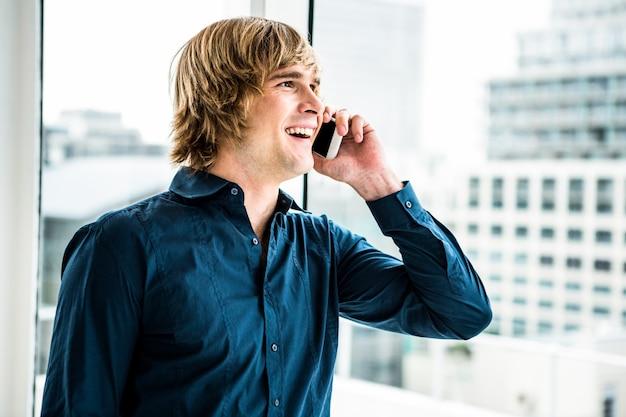 Hipsterzakenman die op de telefoon tegen venster spreken
