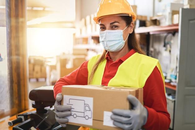 Hispanic magazijnmedewerker vrouw met leveringsdoos terwijl het dragen van veiligheidsmasker - focus op gezicht