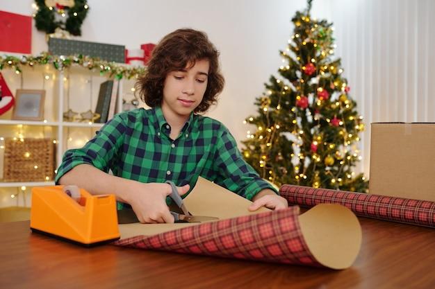 Hispanic tienerjongen zit aan tafel in een kamer ingericht voor kerstmis en snijdt geruit inpakpapier