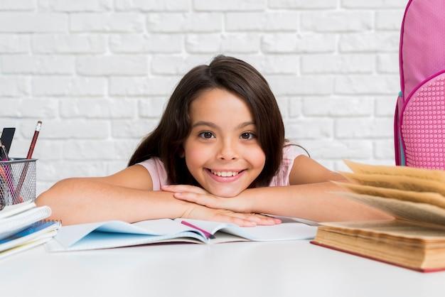 Hispanic vrolijk meisje, zittend aan een bureau
