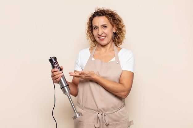 Hispanic vrouw van middelbare leeftijd die vrolijk glimlacht, zich gelukkig voelt en een concept in exemplaarruimte met handpalm toont