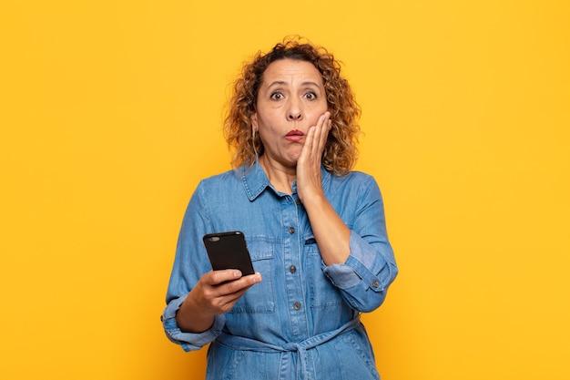 Hispanic vrouw van middelbare leeftijd die zich geschokt en bang voelt, doodsbang kijkt met open mond en handen op de wangen