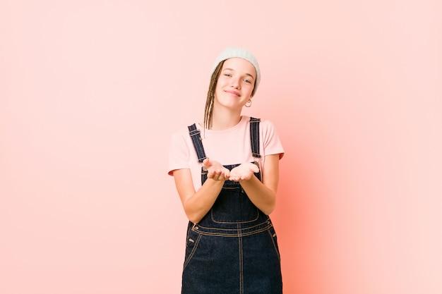 Hispter tienervrouw die iets met palmen houdt, het aanbieden.