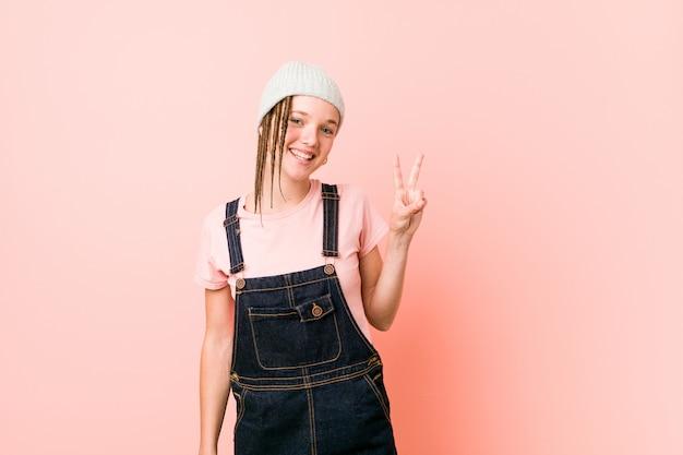Hispter tienervrouw die overwinningsteken toont en breed glimlacht.