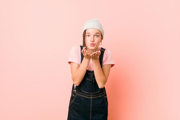 Hispter tienervrouw lippen opvouwen en handpalmen vasthouden om luchtkus te sturen.