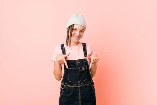 Hispter tienervrouw wijst met vingers naar beneden, positief gevoel.