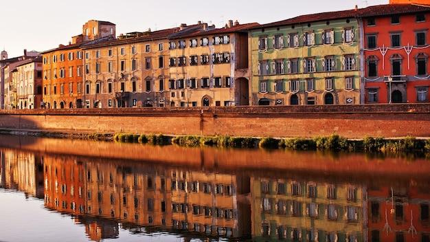 Historische gebouwen langs de rivier de arno in pisa, italië. gevels van de oude italiaanse gebouwen en hun weerspiegeling in het water.