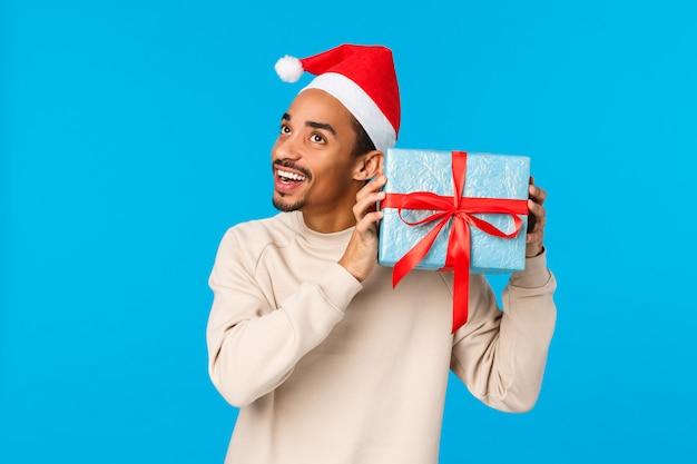 Hmm interessant wat erin zit. nieuwsgierig en enthousiast gelukkig afro-amerikaanse man in kerstmuts, schudden geschenkdoos in de buurt van het oor om te horen en te raden wat het is, glimlachend, wintervakantie vieren