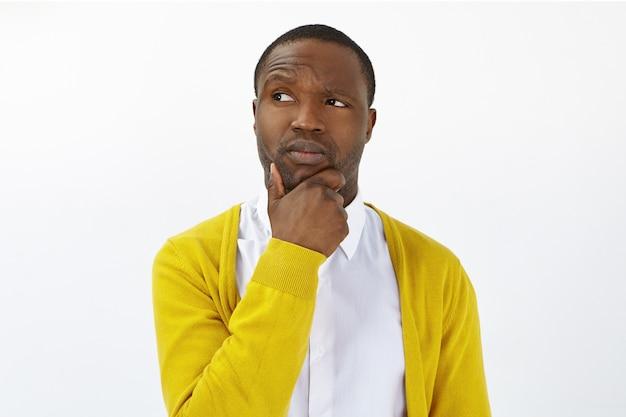 Hmm. laat me denken. stijlvolle jongeman van gemengd ras poseren in studio, kin wrijven, wenkbrauw optrekken en zijwaarts kijken met twijfelachtige onzekere gezichtsuitdrukking, aarzelen om belangrijke beslissing te nemen